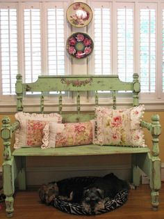 Shabby green bench with floral pillows.
