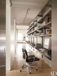 The stainless-steel hall shelving is by E-Z Shelving Systems; the Eames swivel chair is by Herman Miller | archdigest.com