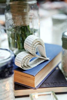 Use book pages to create pretty hearts for centerpieces that show the love. Photo by First Comes Love Photo via Style Me Pretty