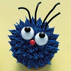 """Monster cupcakes (This little """"monster"""" cupcake looks like Sesame Street's Cookie Monster on Prozac... and we love it! To make this blue monster Halloween cupcake, spoon blue frosting into a decorating bag fitted with a small star tip. Starting on the outside edge, pipe spikes of frosting in concentric circles. Attach white candies for the eyes and mini M's for the pupils. Finish off the monster with a small red candy nose and black shoestring licorice hair.) ~ Free Home Decorating Ideas.Com"""