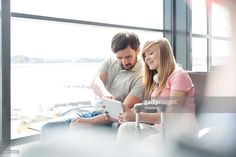 Photo : Father and daughter at airport departure area sharing digital tablet
