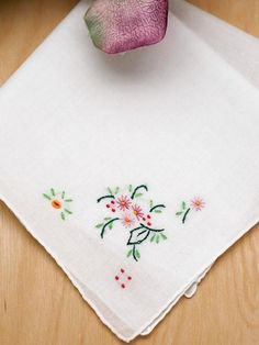 """Set of 3 Holly Embroidered Handkerchiefs The holly inspired flowers in these handkerchiefs are lovely and colorful. They will bring a smile to your face with their bright colors. Each handkerchief has hand rolled edging and a beautiful flower design embroidered in one corner. Made of 100% cotton, each hankie measures approx. 11"""" x 11"""" square and is ideal for small gifts for any occasion."""