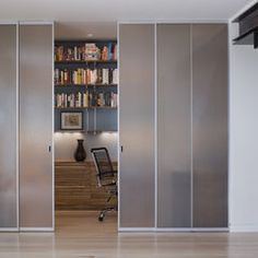 frosted sliding panels hide the built in workspace in this modern home office by John Lum Architecture, Inc. AIA