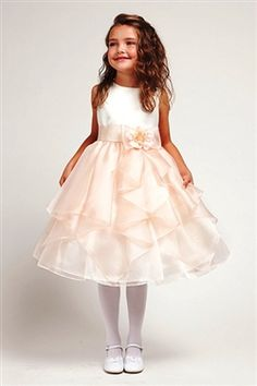 This Gorgeous Ivory Satin bodice dress with Peach ruffled organza skirt is prefect for your Daughter! It comes with a ribbon that ties in the back for an effortless fit, along with a flower accent on the waist that adds a touch of class to this Tea Length dress! She will be able to have the freedom to move while strutting this elegant dress. Its also available in Pink, Ivory/Taupe and White