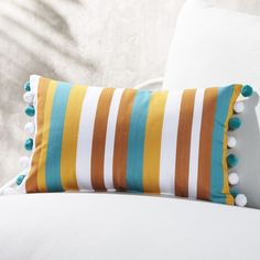 """Free Shipping. Shop 20""""x12"""" Striped Teal and Copper Pom Pom Pillow. Playful pillow stripes the colors of the ocean and the beach across your outdoor seating. Finished on both ends with alternating teal and white pom poms for extra fun. CB2 exclusive."""