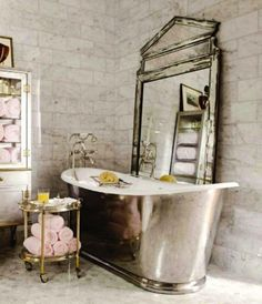 love it.. the marble brick wall, the tub, brass side table and antiqued mirror