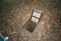 An open trap door leading into the Cu Chi Tunnels in Viet Nam. When closed, the trap door is camoflaged and invisible.