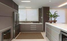 Nessa cozinha de estilo contemporâneo, a distribuição do mobiliário favorece a funcionalidade no ambiente. Os armários altos até o forro, por exemplo, permitem guardar uma grande quantidade de louças. Projeto: Virtu Arquitetura