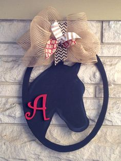 This monogram horse head door hanger/wreath made of wood. Item measures 22 inches tall. Item comes glittered and has a protective finish.
