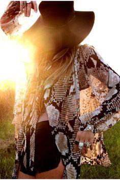 Edgy snake skin blouse, black short and floppy wide brim.