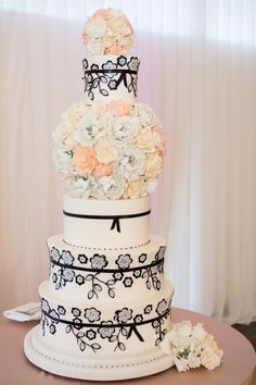 The couple's wedding cake was designed to complement the details of the day. An ebony floral design matched the design on the bride's wedding dress, and sugar flowers paralleled the florals used throughout the ceremony and reception. #FloralWeddingCake Photo by: Carrie Rodman Photography. Read More: https://www.insideweddings.com/weddings/new-england-summer-wedding-by-the-seashore/429/