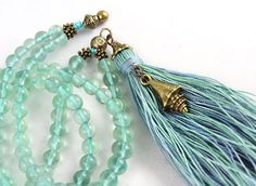 A small antique brass conch shell, aqua green fluorite beads and subtle shades of blue and green in the tassel give this simple mala strand