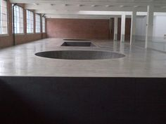 """""""North, East, South, West"""" -- Michael Heizer, colour photograph.  (They absolutely need an overhead view of this in-ground sculpture. """"These four diverse sculptural elements— two stacked cubic forms, one larger and one smaller (North); a cone (South); a triangular trough (West); and an inverted truncated cone (East)—together measure more than 125 feet in length, and sink from the floor of the gallery to a depth of 20 feet. When the work was first developed, such dimensions had no precedent…"""