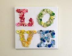 "this is a canvas that spells out ''love"". this is a relly nice and cretiv idea for a canvas. each letter is designed with a differnt colour. the letter is made out of buttons that make it look good."