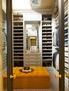 Nate Berkus Design: Glass paneled doors leading to closet with wall to wall storage. Black and white tiled floors, mustard yellow tufted ottoman and mirrored vanity area.