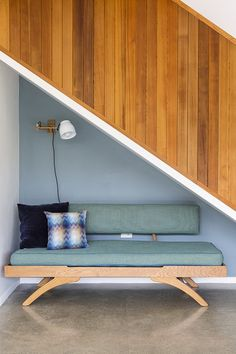Underneath the staircase, there are more details to love. A stylish daybed sits before a feature wall in Resene Blue Bayoux; the trim on the banister is painted in Resene Alabaster. Project by Donnell & Day Architecture. Photo by Duncan Innes. Interior Color Schemes, Interior Paint Colors, Home Interior Design, Colour Schemes, Stairs Feature Wall, Feature Walls, Hallway Inspiration, Wall Paint Colors, Inspirational Wallpapers