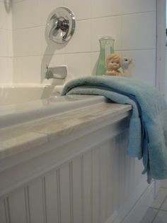 Cover up a boring bathtub with bead board plus threshold marble as a ledge