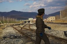 In this Thursday, Nov. 7, 2013 photo, a North Korean soldier steps over the recently opened train tracks linking the city of Rajin, North Korea in the Rason Special Economic Zone to the border at Tumangang and Khasan in Russia. (AP Photo/David Guttenfelder)