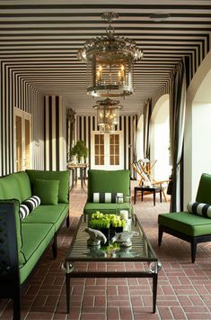 Outdoor covered porch with black and white striped walls and ceiling and kelly green accents