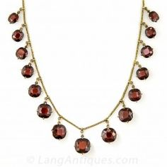 Fifteen gently graduated, dusky cushion-cut almondine garnets dance and dangle, and glisten and glow from this romantic Victorian choker necklace measuring 14 inches long. 14K yellow gold, Circa 1890.