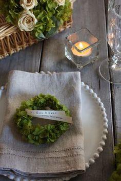 グリーンで作ったミニリースを、ゲストの名前とメッセージを印刷したリボンで結んで、席札にするアイデア。おうちに飾ることもできるので、ゲストにも喜ばれそうですね。