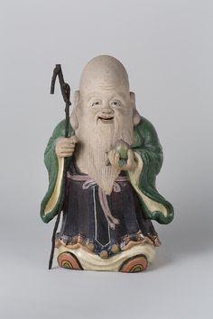 色絵寿星立像 仁阿弥道八 (1783~1855) 江戸時代 高さ72.5cm 仁阿弥道八(二代高橋道八)作の寿星像である。内部に「法橋仁阿弥造」の彫銘、杖は後補。初代・高橋道八の次男として生まれ、兄の早世により29歳で家督相続、京•五条坂に開窯。奥田頴川、宝山文蔵らのもとで修行を積み、青木木米らと共に京焼の名手として知られた。色絵は「尾形乾山、野々村仁清の再来」とまで称され、茶碗などの食器や容器ばかりではなく、生気のこもった精彩な人物や動物などの陶像や磁器像にも名品が多い。仁和寺宮より「仁」、醍醐寺三宝院宮より「阿弥」の号を賜り、出家名「仁阿弥」を称する。45歳の時に紀州藩御庭焼「偕楽園焼」の立ち上げに参画。以後、高松藩御庭焼(賛窯)、薩摩藩御庭焼(磯御庭焼)、角倉家御庭焼(一方堂焼)、西本願寺御庭焼(露山焼)などの立ち上げにも参画。天保13年(1842年)、伏見に隠居するも、以後も「桃山窯」を開窯し作陶を続けた。