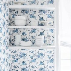 These unassuming kitchen shelves blend into the wall when paired with Caitlin Wilson Design's Indigo Fiore wallpaper, a delicate watercolor floral.