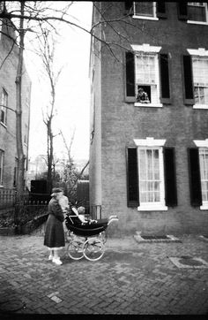 Kennedy family nanny Maude Shaw pushes Caroline in a stroller as Senator Jack Kennedy looks on from the window of his house above.