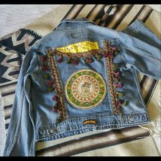 "Levis Denim Jeans Jacket Upcycled Boho Style Levis Jacket Upcycled Embellished with Mayan Calendar Bohemian Gypsy  Boho Women's Denim Jean Jacket.   Embellished with hand sewn leather patches, tasseled edging and military patches. Size XL. Measurements taken flat: Pit to pit - 23"" Shoulder to cuff - 25"" Shoulder - 17"" Waist - 21"" Length - 24"" Levis Jackets & Coats Jean Jackets"