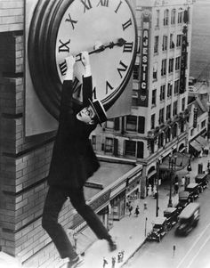 Safety Last! is a 1923 romantic comedy silent film starring Harold Lloyd. It includes one of the most famous images from the silent film era: Lloyd clutching the hands of a large clock as he dangles from the outside of a skyscraper above moving traffic. Harold Lloyd, New Beverly Cinema, Buster Keaton, Silent Comedy, Nostalgia, Silent Film Stars, Movie Stars, Music Tv, Old Movies