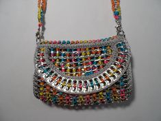 Purse made with pop tabs using blue, pink, orange and yellow variegated nylon yarn. Sewn in metalic silver fabric liner. Small size purse for day-to-day use. Can be used with short strap, long strap and or handheld. Has a magnetic closure. Show your love of recycling. Pop tabs are