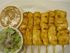 Chicken Satay :Chicken strips grilled on skewers. Served with peanut sauce and cucumber salad.  #Chicken #salad #Awesome Thai #Food forked.com
