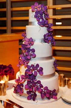 Handcrafted purple sugar orchids are exquisite against a classic white cake with silver bands.