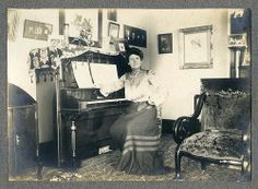 Woman seated at piano in living room