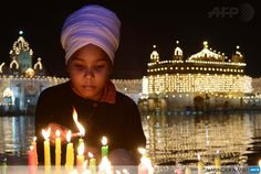 INDIA, Amritsar : An Indian Sikh devotee lights candles at the illuminated Sikhism's holiest shrine Golden Temple in Amritsar on November 2, 2013, on the eve of Bandi Chhor Divas or Diwali. Sikhs celebrate Bandi Chhor Divas or Diwali to mark the return of the Sixth Guru, Guru Hargobind Ji, who was freed from imprisonment and also managed to release 52 political prisoners at the same time from Gwalior fort by Mughal Emperor Jahangir in 1619. AFP PHOTO/NARINDER NANU