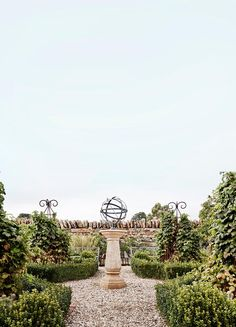 """The wall around this parterre garden was built by Cameron using local 'paddock rock'. At the centre, an armillary sphere sits atop an octagonal sandstone sundial, both from Provincial Antiques. To the sides, obelisks covered in thornless raspberries are encircled by English box hedge. """"The raspberry bushes are prolific,"""" says Debbie. """"I used to make raspberry cordials with them, which our boys sold under the banner of Wilson Brothers Cordials at the farmers' market."""""""