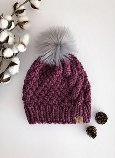 Chunky Cable Knit Hat in the beautiful color: Fig -Comfy, Slightly Slouchy Fit -Made with quality wool/acrylic yarn -5 Fluffy Gray Pom Pom on top; or choose not to add a pom pom, if you prefer. -Soft ultrasuede fold-over tag added to lower edge for a professional look! **Please see