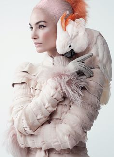 Pecking Order - The house of McQueen has a tradition of playing with aviary themes. Here the fine, feathery, layered jacket is subtle in every way (less so the salmon-crested cockatoo). Model Lily Aldridge wears an Alexander McQueen palest-pink mink-and-shredded chiffon coat; 212.645.1797 for information. Fendi leather-and-goat-fur gloves.
