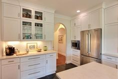 White shaker style kitchen cabinets with brushed nickel drawer pulls give this kitchen an elegant, contemporary look. Glass paneled cabinets break up the solid white cabinets and allow vintage tea kettles to show.