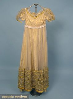 "Silk and net ballgown, c1815; One-piece cream net over yellow shot silk under dress, short puff sleeves and hem, trimmed with goldenrod yellow ""peacock eyes"", yellow satin piping and rouleau hem, B 32"", Hi-W 28"", L 51"""