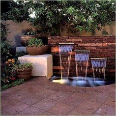 Belle fontaine de jardin entourné de carrelage en pierre