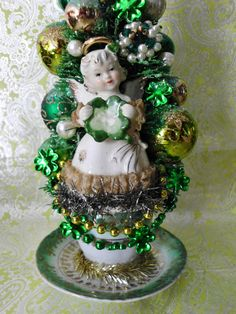 LAUGHTER AND LEMONDROPS - CAROLINE M. SHERMAN  This is a one of a kind handmade creation by artist Caroline Sherman of Laughter and Lemondrops. It is an adorable vintage inspired St. Patricks Day creation with a St. Patricks Day themed Bottle Brush Tree. It is absolutely adorable! The tree is attached to an antique piece of green and gold pottery. In the front of the tree is a little lefton angel girl holding a shamrock. This piece measures approximately 14 tall & 5 wide. Signed by Caroli...