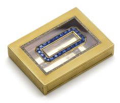 A sapphire and diamond box of rectangular form, the lid inset with a clear plaque set with square- and trilliant-cut sapphires within a frame of rose-cut diamonds, to an engine turned ground.French assay and makers mark.