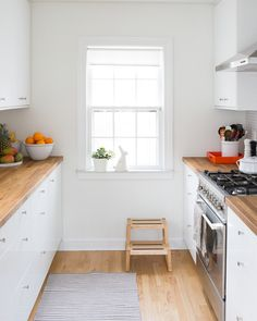 Love the butcher block counter with the white cabinets and the throw rug for the laundry room.
