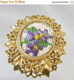 This #vintage needlepoint violets brooch pendant is just stunning!  This beautiful piece of art consists of an oval petit point embroidered cameo filled with purple and lave... #ecochic #etsy #jewelry #jewellery