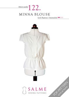 Elastic waist blouse featuring pleat detail at front and structured sleeves. Button closure at back...
