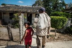 Yulien Diaz Hernandez, right, a farmworker for a private sugar cane farm, is greeted by his son Leyson Ardiel, 5, after Yulien returns home ...