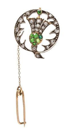 A Victorian era brooch in the shape of a thistle, with diamonds and demantoid garnets in silver topped gold.