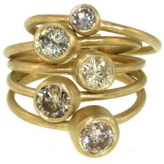 The diamonds in this signature L Frank ring are so stunning! They are old European cut, with a range from silver to cognac, and feature 4, 5, and 6mm stones set simply in 18k yellow gold. Each stone sits atop a 1mm thick band, which are joined in the back by a thin bar. The ring measures approximately 18mm wide in the front, tapering to a very comfortable 7mm in the back. It weighs 11.60g of 18k gold, and the diamonds weigh approximately 2.14ctw. The ring is available in a size 5.75, ...