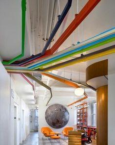 Pomysłowa dekoracja sufitu - kolorowe stalowe rury na suficie